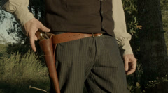 cowboy fires pistol and puts in holster - stock footage