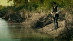 Cowboy shoots at something in the water Stock Footage