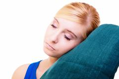 sleepy blond girl with green pillow isolated over white - stock photo