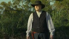 Cowboy walks in scene Stock Footage
