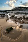 summer landscape with rocks on beach during late evening and low sunlight - stock photo