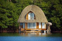 Thatched bungalow over water Stock Photos