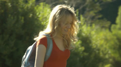 Happy Young Blonde Woman Crosses A Stream Stock Footage
