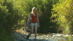 Pretty Young Blonde Woman Crosses A Stream Stock Footage