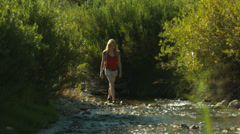Pretty Young Blonde Woman Approaches Up A Stream Stock Footage