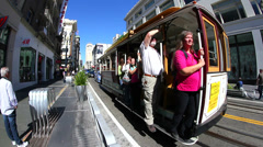 Cable car departing down street in San Francisco Stock Footage