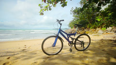 Blue modern mountain bike parked on a tropical beach Stock Footage