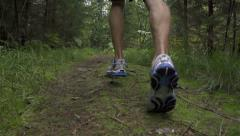 SLOW MOTION: Close up male running through the woods - stock footage