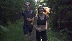 SLOW MOTION: A young couple jogging through the woods - stock footage