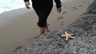 Stock Video Footage of Woman finding a star fish on beach rocks