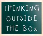 Stock Illustration of thinking outside the box phrase, handwritten with white chalk on a blackboard