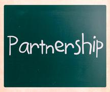The word 'partnership' handwritten with white chalk on a blackboard Stock Photos