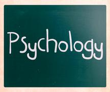 The word 'psychology' handwritten with white chalk on a blackboard Stock Photos