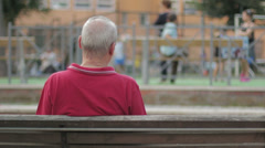 Elderly man's on a bench, backfacing. In park Stock Footage
