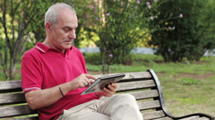 Retired senior man resting and using his tablet at table in park - stock footage