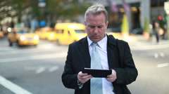 Caucasian middle aged businessman using tablet pc in New York City Stock Footage