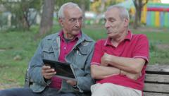 Old man teaching his elderly friend to use a new tablet PC Stock Footage