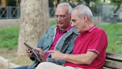 Old man teaching his elderly friends to use a new tablet PC Stock Footage