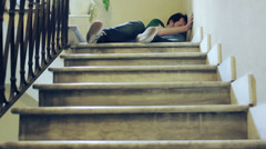 Unconscious man lying on a staircase - stock footage