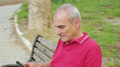 Old Man relaxing using tablet in park - stock footage