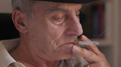 Elderly man thinking about problems and smokes a cigarette Stock Footage