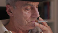 Stock Video Footage of elderly man thinking about problems and smokes a cigarette