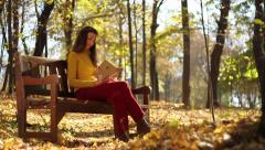 Young woman reading on bench autumn colors park - stock footage