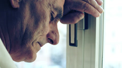 Sad old man near window - stock footage