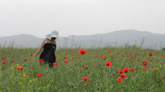 Woman with white hat walk in poppies field in bloom Stock Footage