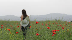 Young lady with big hat walk in blossom red poppies field and pick up flowers - stock footage