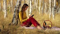 Beautiful young woman with tablet computer park relaxing reading Stock Footage