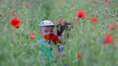 Sweet baby and his mother spend time together in flourish red poppies field Stock Footage