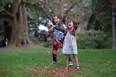 Little Girls Throw Pile Of Petals In The Air - stock photo