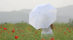 Beautiful young lady with a white umbrella enjoy in red poppies flourish field Stock Footage