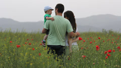 Young family spend time together in flourish red poppies field - stock footage