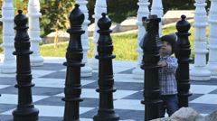 Lovely baby child looking to big chess pieces from a big chessboard  Stock Footage