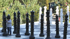 Little cute baby step on big chessboard Stock Footage