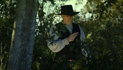 Cowboy checks watch and pistol Stock Footage