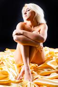 Young naked slim women sitting on yellow cloth Stock Photos