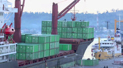 Crane loading shipping containers onto ship at wharf time lapse Stock Footage