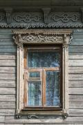 Old wooden window with carved architraves Stock Photos