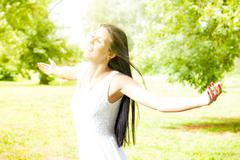 Stock Photo of happiness young woman with sprading hands enjoyment in the nature