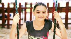 Stock Video Footage of Teenage girl on swing smiling at camera