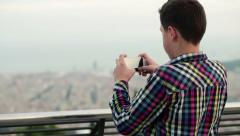 Boy taking picture of city view with his smartphone HD Stock Footage