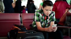 Young boy texting on his smartphone at the airport HD - stock footage