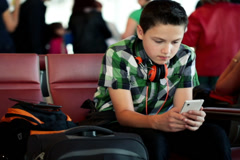 Young boy texting on his smartphone at the airport NTSC - stock footage