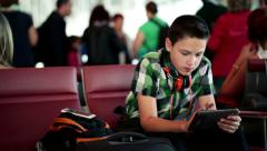 Young boy using his tablet at the airport HD Stock Footage