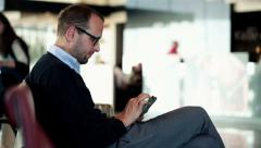 Profile of businessman working on his tablet at the airport HD Stock Footage