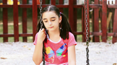 Sad young girl sits on swing Stock Footage