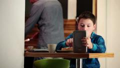 Boy using tablet, eating breakfast at the kitchen table HD Stock Footage